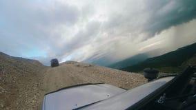 Jedzie samochód ciężkiego na wysokiej góry drodze na chmurnym dniu Auto podróż: POV - punkt widzenia SUV jedzie dolinę z zdjęcie wideo