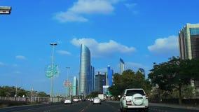 Jedzie w Abu Dhabi miasta corniche sławnej drodze z widokiem nowożytni drapacz chmur przeciw niebieskiemu niebu i chmurom zbiory