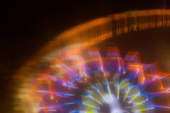 Jedzie w ruchu przy parkiem rozrywkim, nocy iluminacja długo ekspozycji zdjęcia stock