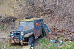 Jeep aherrumbrado abandonado en el bosque Fotos de archivo