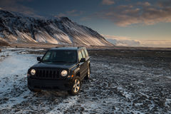 A jeep by an amazing landscape. A jeep stops by a beautiful mountain in Iceland at sunrise royalty free stock images