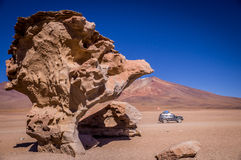 Jeep at Arbol de Piedra near Uyuni. Jeep driving past Arbol de Piedra rock formations, a popular stop on tours for tourists visiting Uyuni region Stock Image
