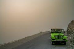 Jeep auf einer Gebirgsstraße während des Sturms Lizenzfreie Stockfotos