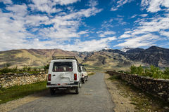 Jeep Caravan bilar på vägen med sikt av Zanskar Arkivbilder