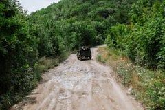 Jeep che guida su una strada nelle montagne Immagini Stock Libere da Diritti