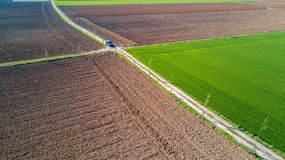 A jeep crossing a country road, off-road aerial view of a car traveling a dirt road through the fields. Stock Photos