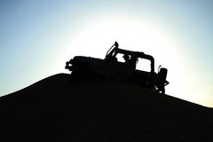 Jeep Crusing in Desert. A silhouette effect of a man cursing his jeep in the desert sand dunes Royalty Free Stock Photo