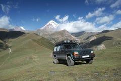 Jeep in de bergen. Zet Kazbek op Royalty-vrije Stock Afbeelding