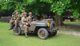 Jeep de la guerra mundial 2 con los hombres vestidos como soldados americanos de la guerra mundial 2 Fotos de archivo libres de regalías