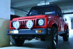 Jeep del color rojo con las luces de niebla Fotos de archivo libres de regalías