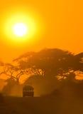 Jeep del safari que conduce a través de sabana en la puesta del sol Foto de archivo libre de regalías