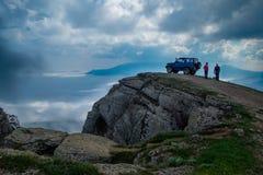 Jeep, der auf einem Felsen über den Wolken steht Stockbild
