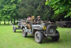 Jeep des Weltkrieg-2 mit den Männern gekleidet als Soldaten des Weltkrieg-2, Gewehr schleppend Stockbild