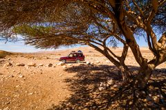 Offroad jeep safari vehicle parked in the middle of the desert Royalty Free Stock Photo
