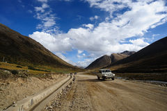 Jeep on dirt road. A jeep traveling on the highway of G318, from Sichuan to Tibet, China royalty free stock photo