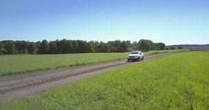 Jeep drives along grey ground road against green field stock footage
