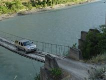 A jeep drives over a rope bridge over a river. In Turkey d.y Stock Images