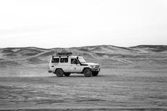 Jeep driving in sand dunes in desert, Hurghada, Egypt. Hurghada, Egypt - February 26, 2017: jeep driving in sand dunes in desert on white sky background. Safari royalty free stock photo