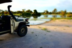 Jeep for a good Safari in Botswana. This jeep is taken in front of a nice waterhole Stock Images