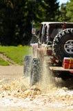 Jeep grande que salpica fango en las montañas Imágenes de archivo libres de regalías