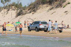 Jeep with insolent driver rides on the beach with holidaymakers Stock Photography