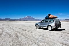 Jeep in the landscape of the Salar de Uyuni and lagoons like Lag. Una Verde or Laguna Colorada in the national park in Bolivia. Several species of birds and Stock Photo