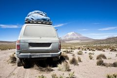 Jeep in the landscape of the Salar de Uyuni and lagoons like Lag. Una Verde or Laguna Colorada in the national park in Bolivia. Several species of birds and Royalty Free Stock Photo