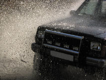 Jeep passes through the water creating large spray of water Royalty Free Stock Photo