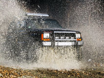 Jeep passes through the water creating large spray of water Royalty Free Stock Images