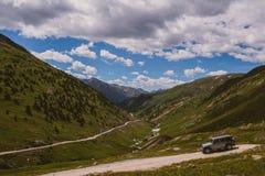 Jeep que conduce a través de las montañas Imagenes de archivo