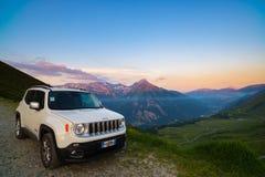 Jeep Renegade blanco parqueó en el camino de tierra en el punto de visión panorámica en las montañas italianas desde arriba Cielo Imagen de archivo libre de regalías