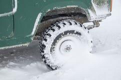 Jeep`s tire in snow in winter. Closeup stock photo