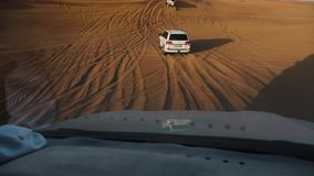Jeep Safari in the Arabian desert. Car view on jeeps driving among desert tracks at sunset. DUBAI UNITED ARAB EMIRATES - JANUARY 12 2019: Jeep Safari in the stock video footage