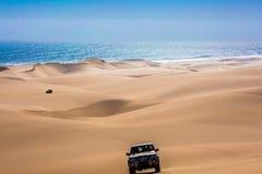 Jeep - safari through the sand dunes. Fantastic jeep - safari through the huge sand dunes on the ocean shore. Atlantic coast of Namibia, south of Africa. The royalty free stock photo