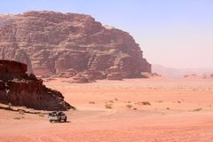 Jeep safari in Wadi Rum desert, Jordan. Middle East. Tourists in the car ride on off-road on sand among the beautiful rocks royalty free stock photography