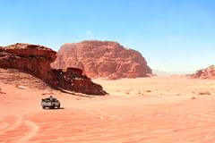 Jeep safari in Wadi Rum desert, Jordan. Tourists in the car ride on off-road on sand among the beautiful rocks royalty free stock image