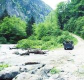 Jeep su altezza della strada in montagna, bello paesaggio di estate con il fiume immagine stock