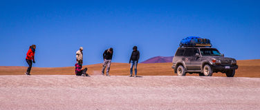 Jeep tourists have a rest in the dessert. A Jeep Tour through the Bolivian Salt Desert Uyuni is a popular touristic activity on the Altiplano in Bolivia Royalty Free Stock Image