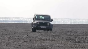Jeep Wrangler on Icelandic terrain. VIK, ICELAND - MAY 03, 2018. Jeep Wrangler Unlimited four wheel drive vehicle being used on terrain on a black sand beach in stock video