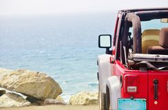 Jeep wrangler mountain ocean beneath. Jeep Wrangler on the edge of mountain road and beneath is ocean and  ocean view  ahead as symbol of car tourism which is Royalty Free Stock Photos