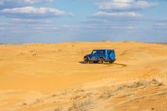 Jeep Wrangler Rubicon Unlimited azul em dunas de areia do deserto Fotografia de Stock Royalty Free