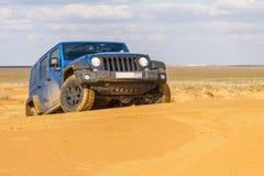 Jeep Wrangler Rubicon Unlimited azul em dunas de areia do deserto Foto de Stock Royalty Free