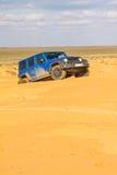 Jeep Wrangler Rubicon Unlimited azul em dunas de areia do deserto Fotos de Stock Royalty Free