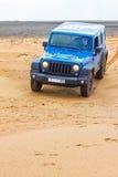 Jeep Wrangler Rubicon Unlimited azul em dunas de areia do deserto Imagens de Stock Royalty Free