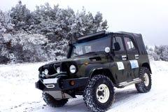 Jeeping, die in aard in een sneeuw, de winterbos reizen stock foto's