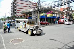 A Jeepney taxi drives down the street/road in downtown Manila with designs and colourful decorations on the vehicle royalty free stock photography