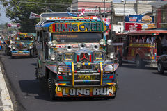 Jeepneys passing, Filipino inexpensive bus service. Jeepneys are the most popular means of public transportation in the Philippine Stock Image