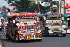 Jeepneys passing, Filipino inexpensive bus service. Royalty Free Stock Images