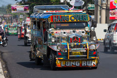 Jeepneys passing, Filipino inexpensive bus service. Philippines. Royalty Free Stock Photos