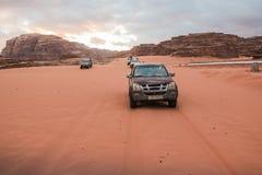 Jeeps et touristes bédouins de voiture du ` s dans lui en désert de Wadi Rum en Jordanie Photographie stock libre de droits